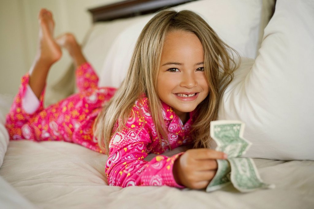 Hawaii, Young girl collecting tooth fairy money from under pillow. : Stock Photo