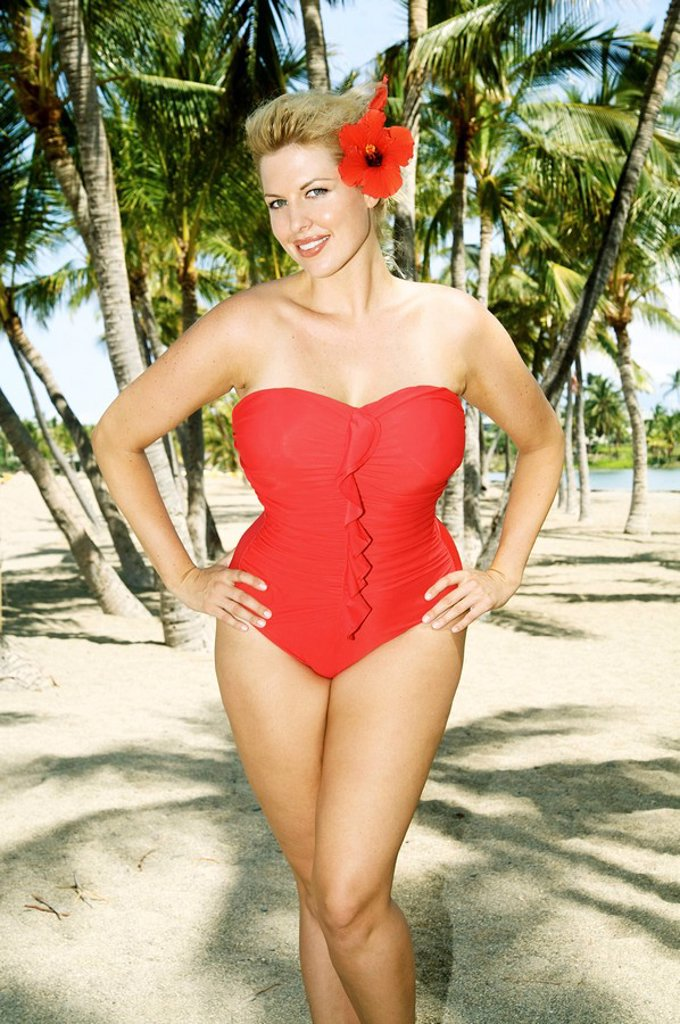 Hawaii, Big Island, Kona, Beautiful woman on beach wearing red swimsuit. : Stock Photo