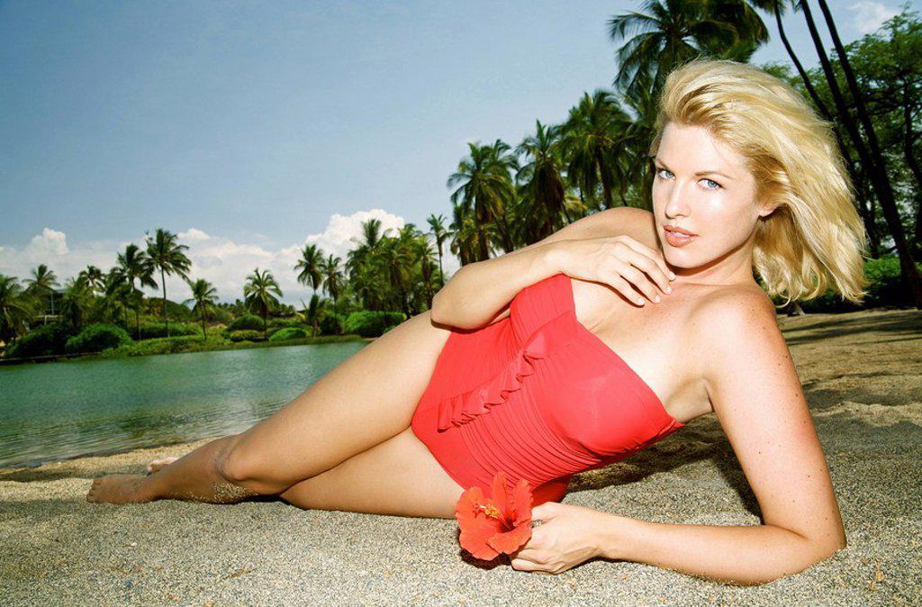 Stock Photo: 1760-14053 Hawaii, Big Island, Kona, Beautiful woman lounging along beach wearing red swimsuit.