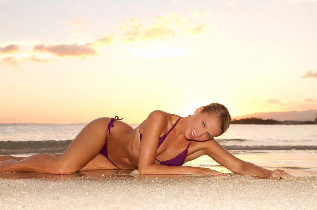 Stock Photo: 1760-14070 Hawaii, Oahu, Blond woman lounging on beach, Sunset light.