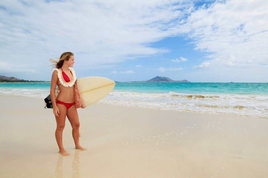 Stock Photo: 1760-14101 Hawaii, Oahu, Kailua Beach, Teenage girl holding surfboard on beach.