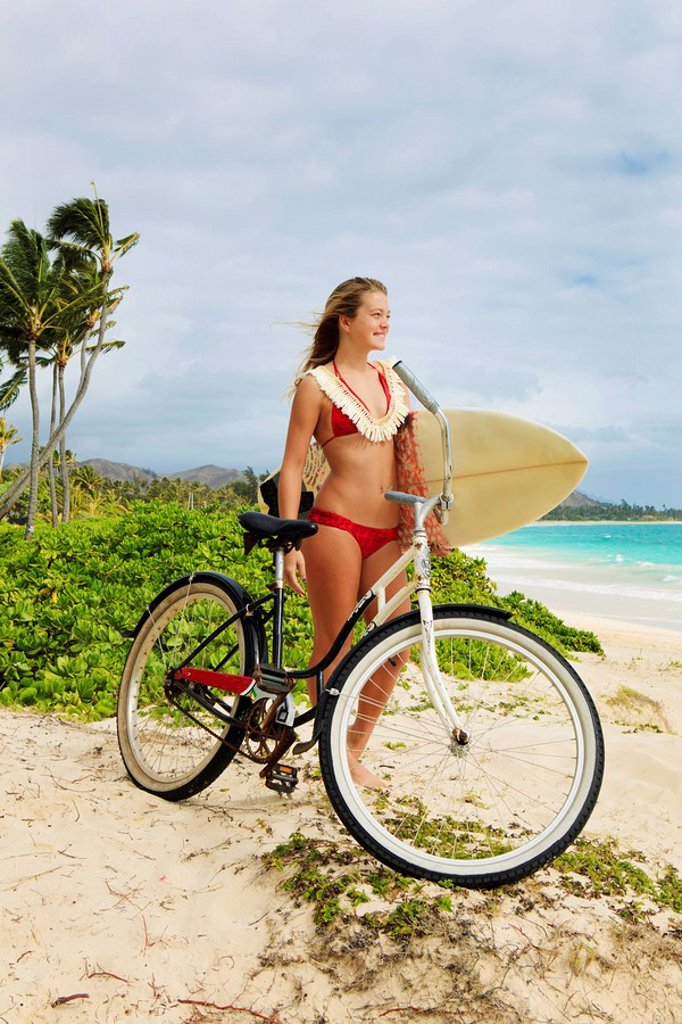 Hawaii, Oahu, Kailua Beach, Teenage girl with surboard and bike. : Stock Photo