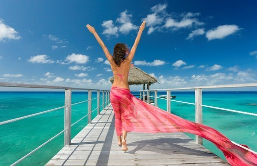 Stock Photo: 1760-14107 French Polynesia, Tuamotu Islands, Rangiroa Atoll, Woman walking down ocean pier wearing pink pareo, View from behind.