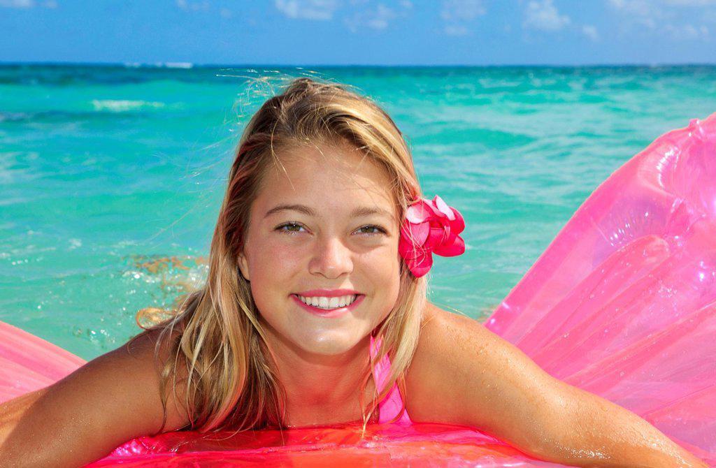 Hawaii, Teenage girl in ocean with inflatable. : Stock Photo