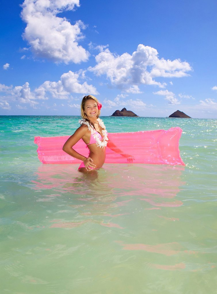 Hawaii, Oahu, Kailua, Lanikai Beach, Teenage girl in ocean with inflatable. : Stock Photo