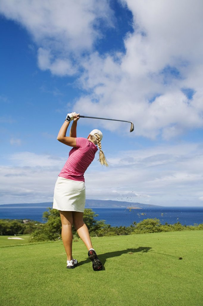 Stock Photo: 1760-1415 Hawaii, Maui, Wailea Gold Golf Course, Female golfer swinging golf club, view from behind.