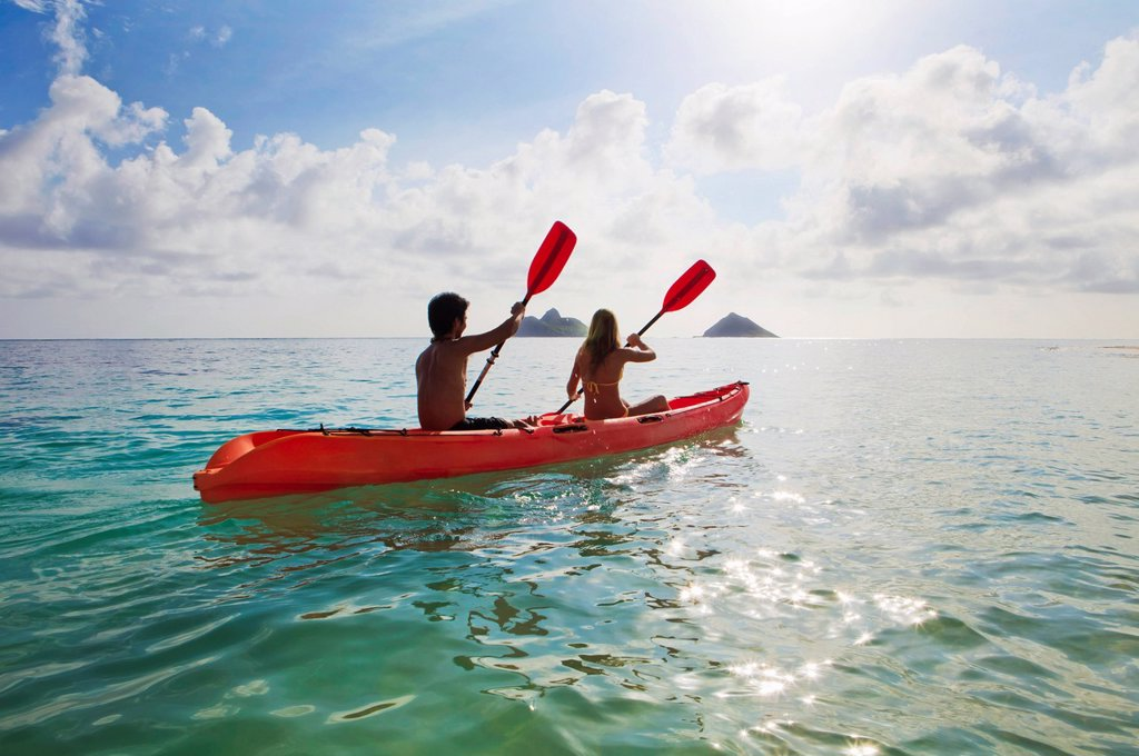 Hawaii, Oahu, Young couple kayaking off Lanikai Beach, Mokulua Islands in distance. : Stock Photo