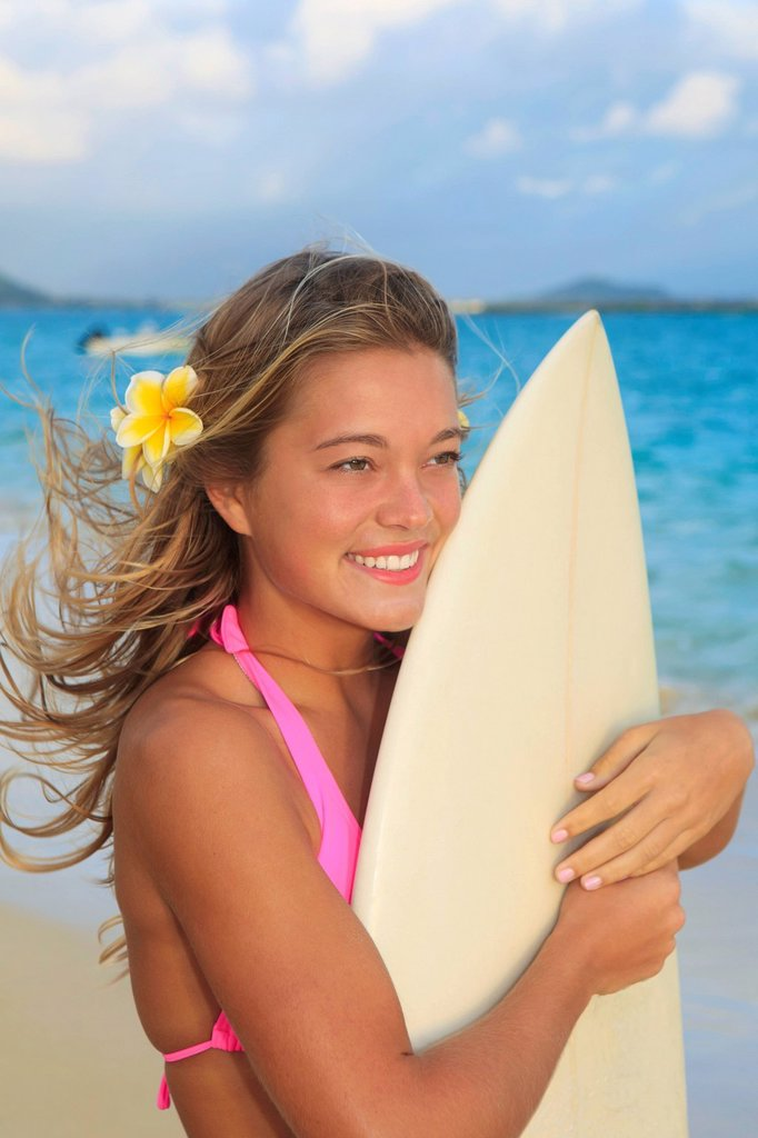 Hawaii, Oahu, Lanikai, Blond surfer girl with surfboard along beach. : Stock Photo
