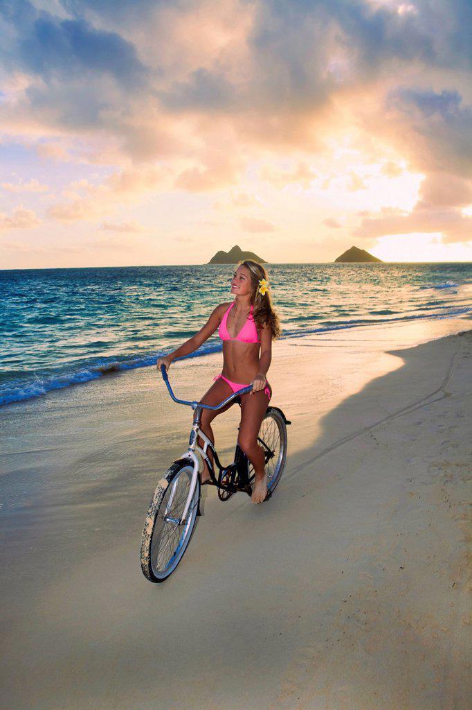 Stock Photo: 1760-14597 Hawaii, Oahu, Lanikai, Blond girl riding bike along beach.