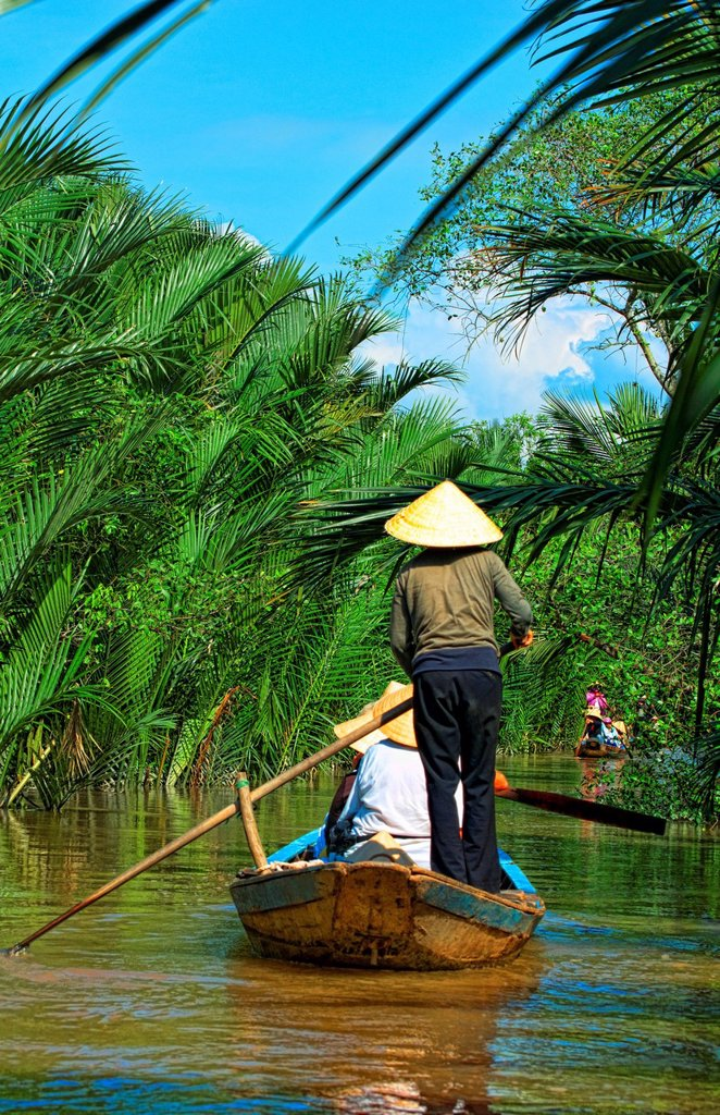 South East Asia, Vietnam, Saigon, Mekong Delta River, Women paddle down a muddy river. : Stock Photo