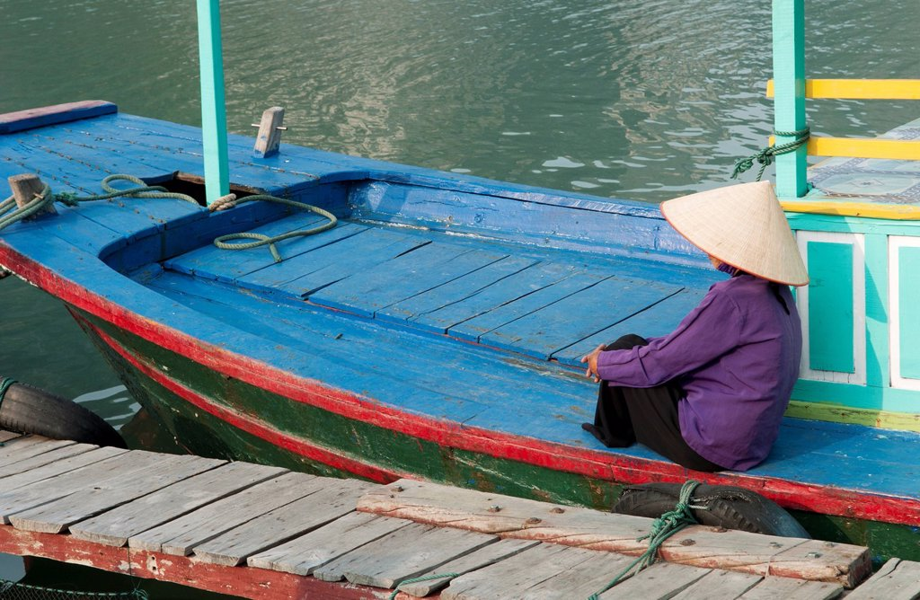 South East Asia, Vietnam, Ha Long Bay, Portrait of a Vietnamese woman sitting on docked fishing boat, side view. : Stock Photo