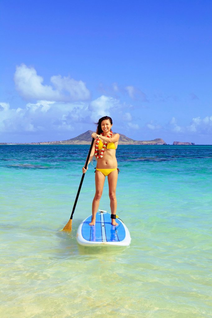 Hawaii, Oahu, Lanikai, Asian women paddle boarding off the beach near Mokulua Island. : Stock Photo
