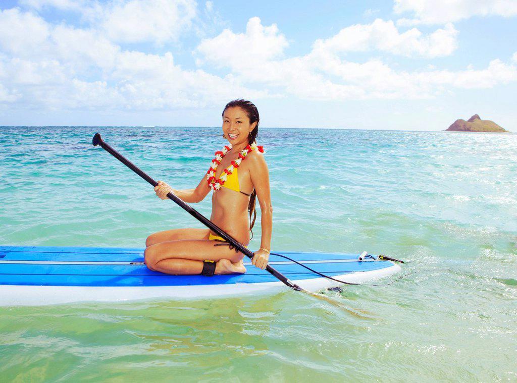 Hawaii, Oahu, Lanikai, Asian women paddle boarding off the beach near Mokulua Island. : Stock Photo