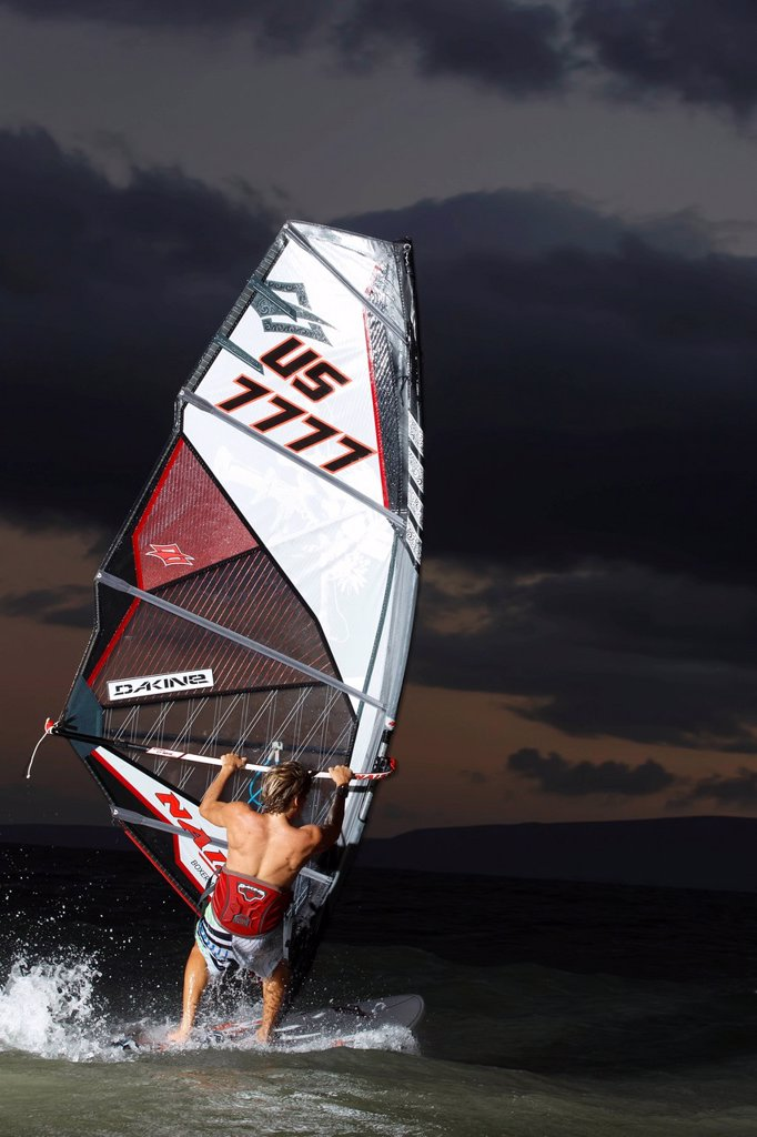 Hawaii, Maui, Kihei, Professional windsurfer Dean Christener sailing at sunset. FOR EDITORIAL USE ONLY. : Stock Photo