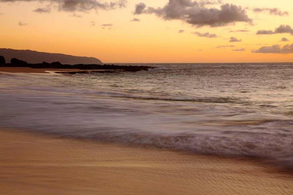 Hawaii, Blur of waves crashing on the beach at sunset : Stock Photo