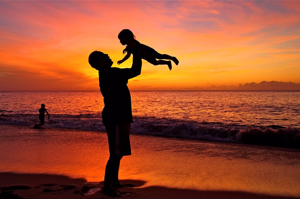 Silhouette of father and child on the beach : Stock Photo