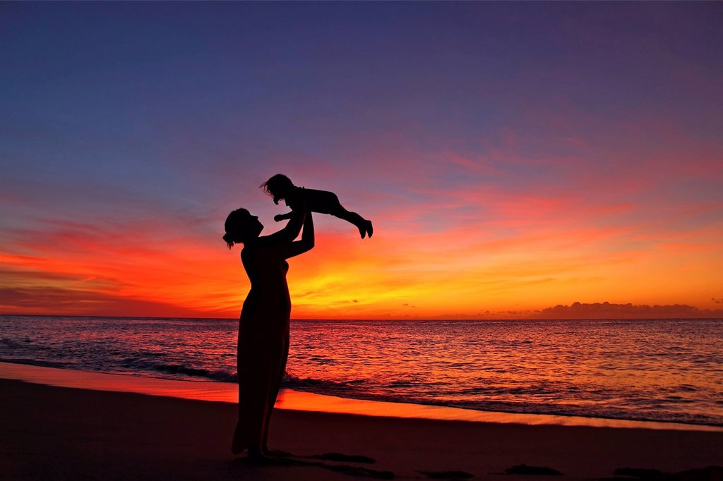 Silhouette of a mother and child on the beach : Stock Photo
