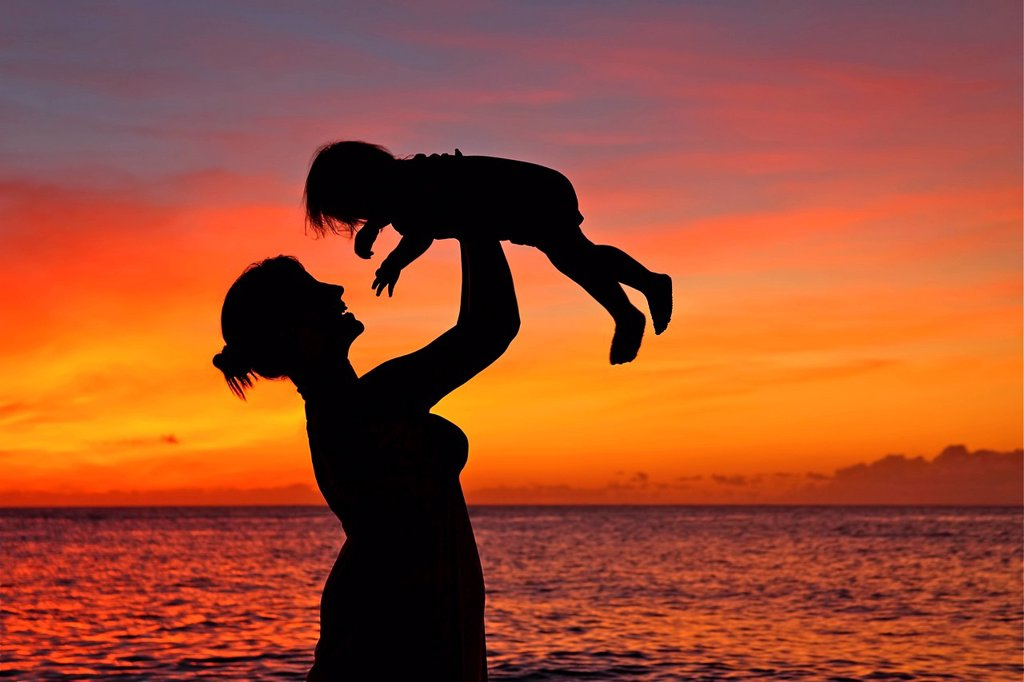 Silhouette of a mother and child on the beach. : Stock Photo