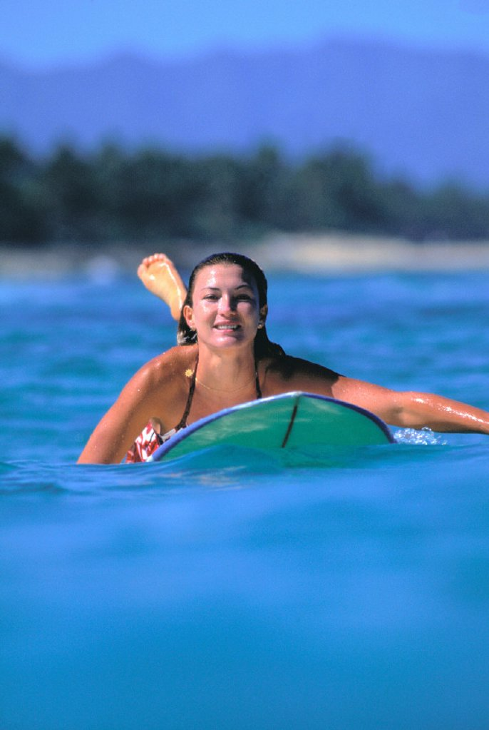 Front view of woman on surfboard paddling out, smiling : Stock Photo