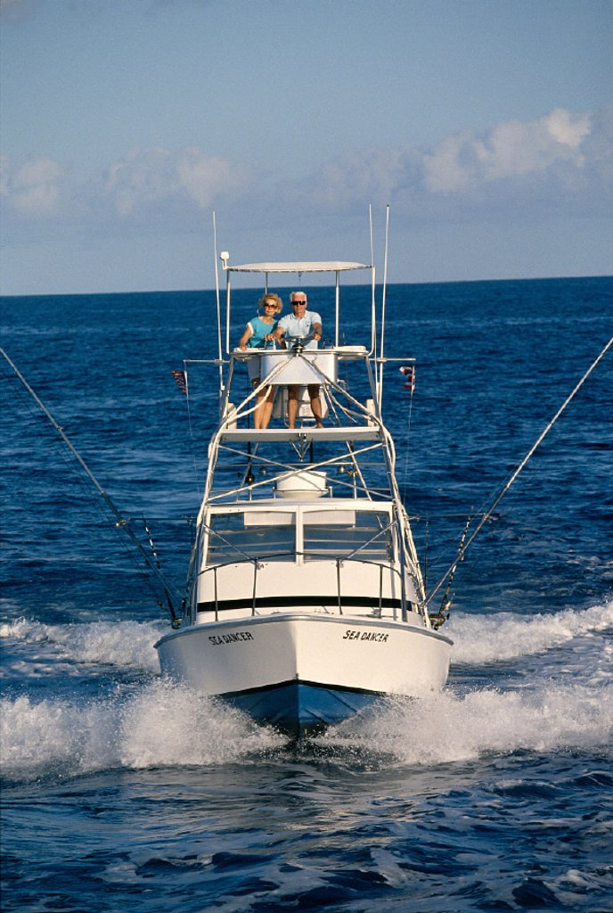 Hawaii, front view of sport fishing boat, senior couple in flying bridge A14E : Stock Photo