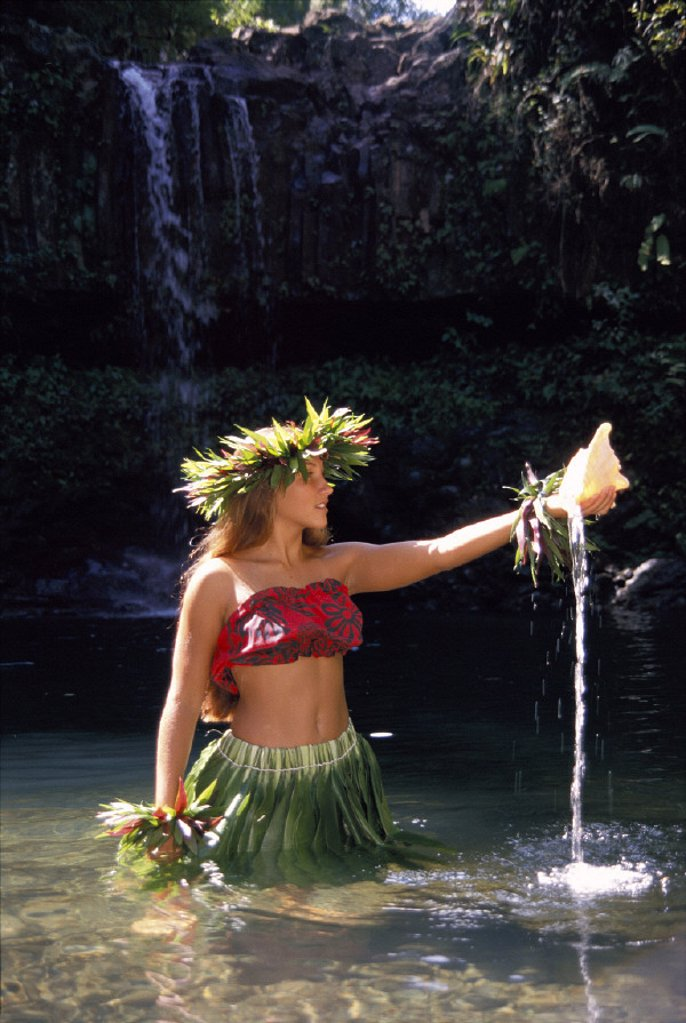 Stock Photo: 1760-22813 Hula dancer in water, holding shell, waterfall in background