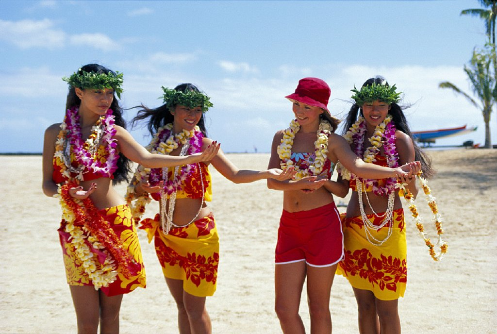 Three Hawaiian women teach visitor to dance hula, all wear leis & smiling, beach : Stock Photo