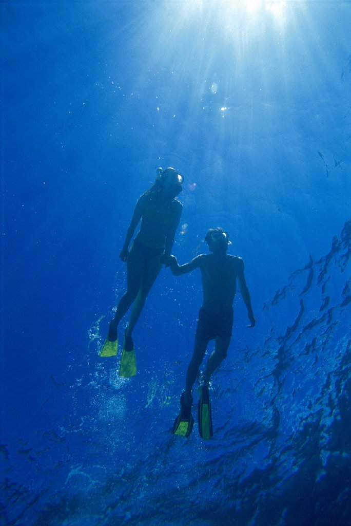 Hawaii view fr beneath couple snorkel @ surface, sunburst sunrays D1363 Pacific Ocean : Stock Photo