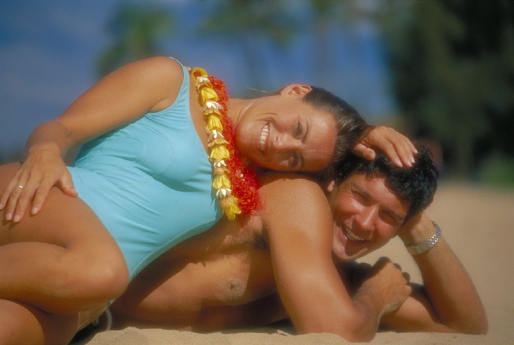 Hawaii Maui Makena couple lay on beach woman atop man smile together, lei D1060 : Stock Photo