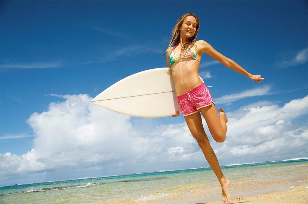 Hawaii, Kauai, Tunnels Beach, Surfer girl enjoying a day out. : Stock Photo