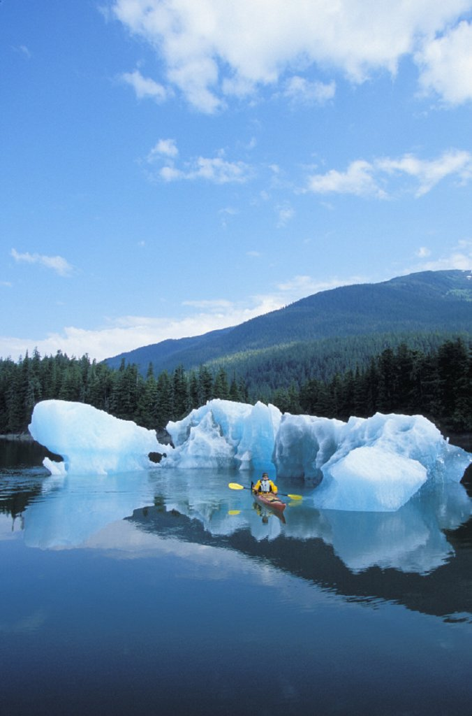 Alaska, Tongass National Forest, Tracy Arms Terror Wilderness, Kayaker passing through icebergs. : Stock Photo