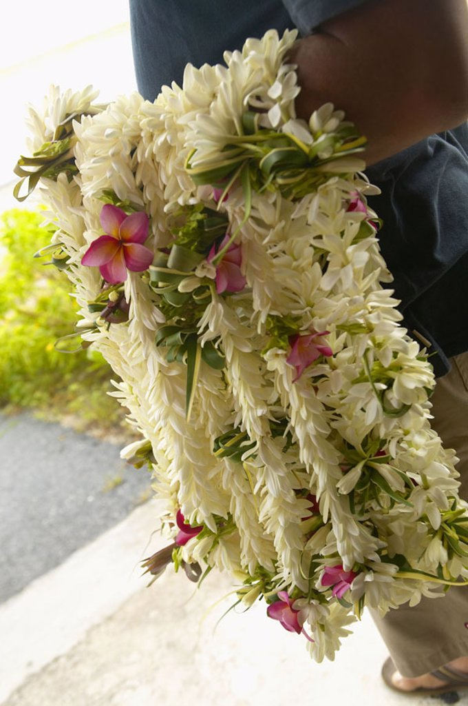French Polynesia, Tuamotu, Close-up of many leis hanging on a mans arm at the airport : Stock Photo
