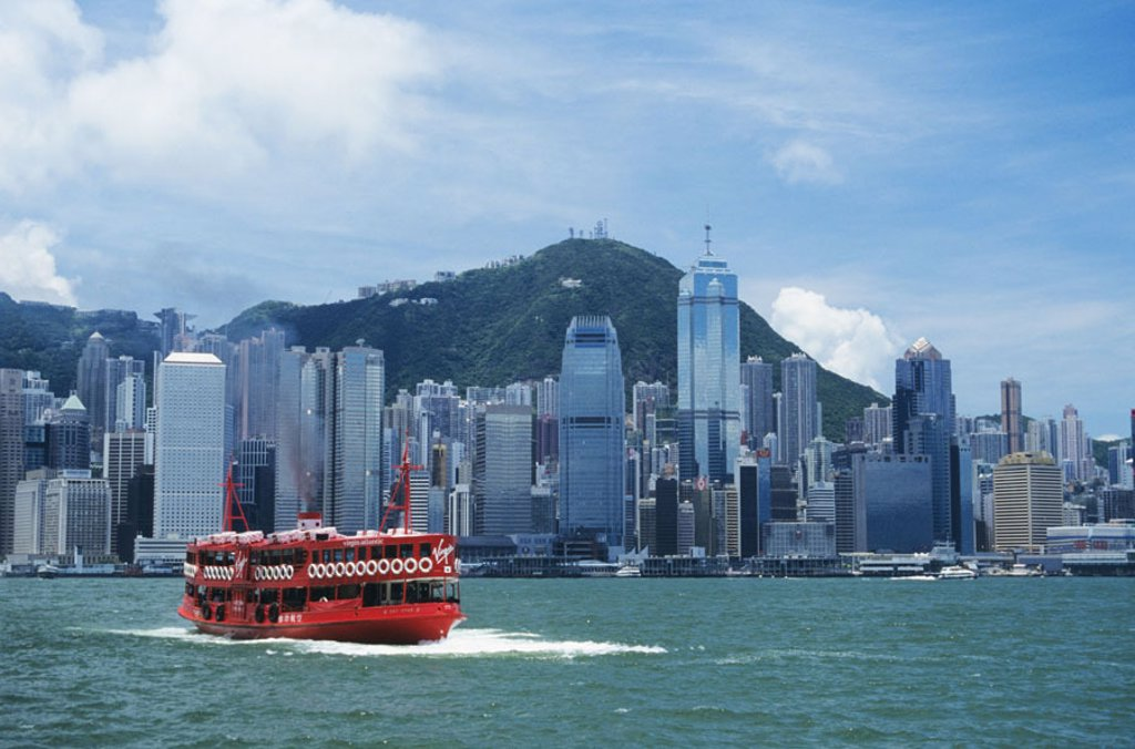 Hong Kong, Hong Kong Harbor, view of business district with large red Virgin Atlantic ferry in foreground. : Stock Photo