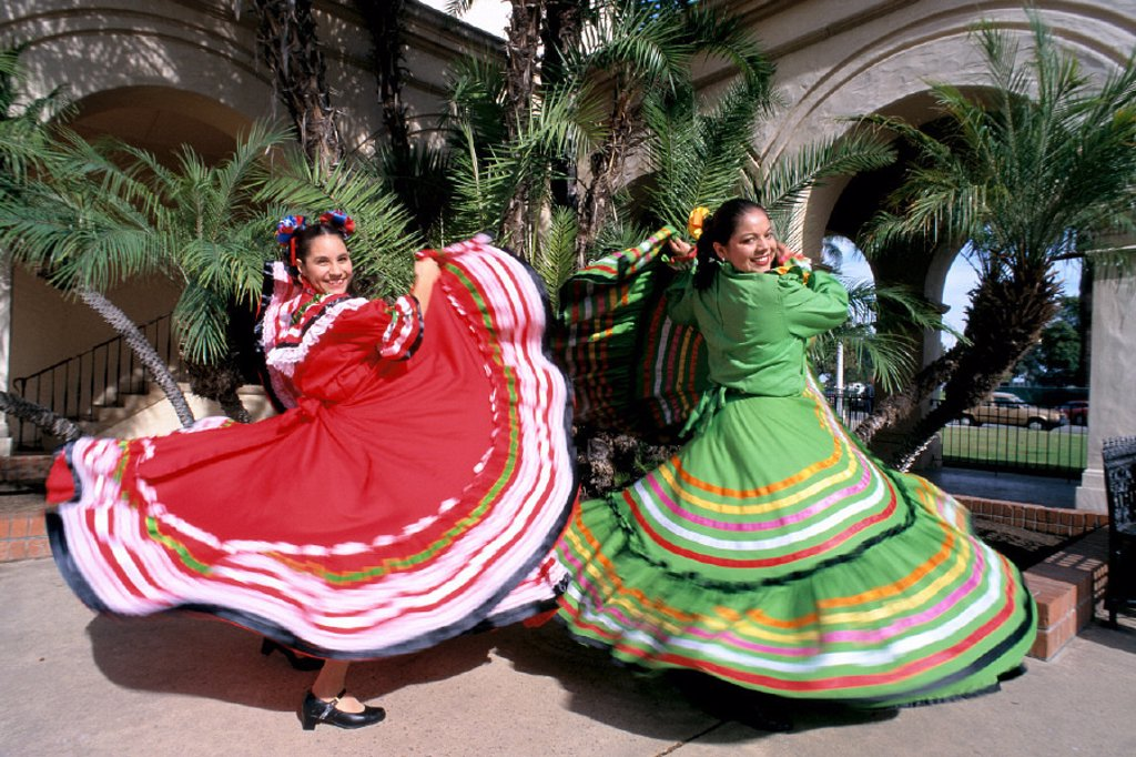 Full length view of two smiling women in colorful traditional dress, twirling : Stock Photo