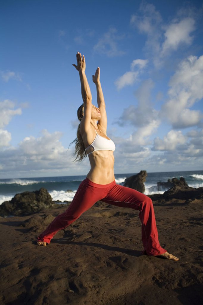 Hawaii, Maui, young woman doing yoga next to the ocean. : Stock Photo