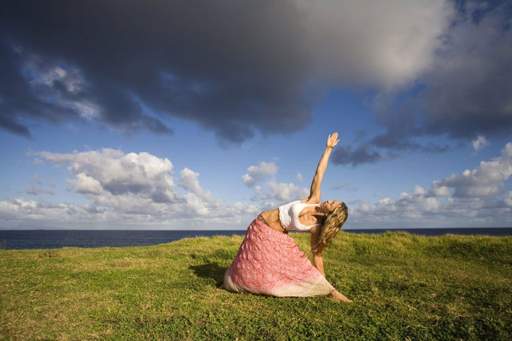 Hawaii, Maui, young woman doing yoga on grassy hill next to the ocean. : Stock Photo
