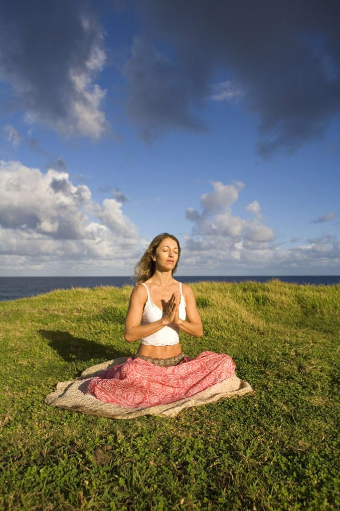Stock Photo: 1760-3591 Hawaii, Maui, young woman doing yoga on grassy hill next to the ocean.