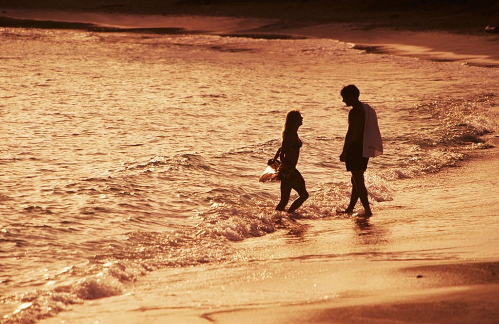 Caribbean, Couple wading in ocean along beach at sunset : Stock Photo