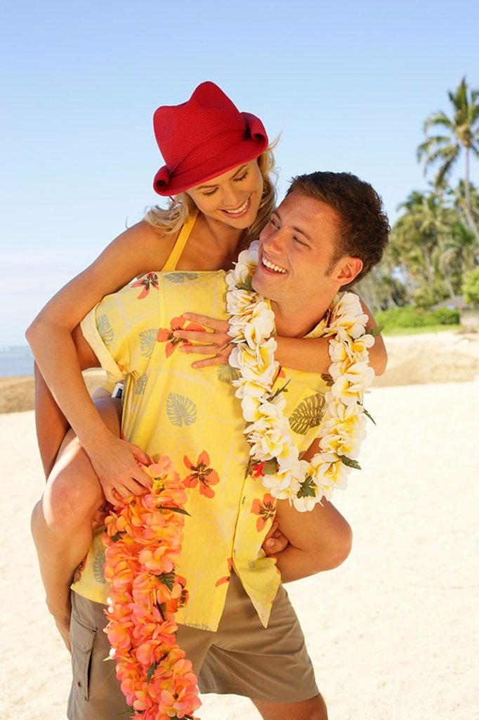 Stock Photo: 1760-4361 Hawaii, couple enjoying sunny day on beach, man carrying woman on back