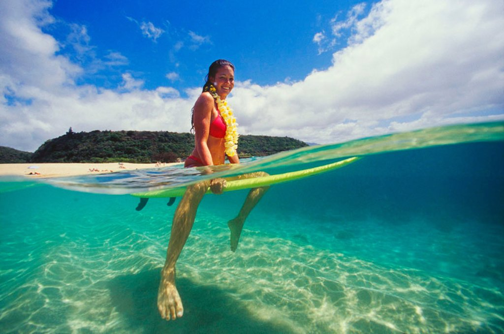Stock Photo: 1760-4499 Over/Under shot of sexy surfer girl sitting on her board out in the ocean, wearing lei.