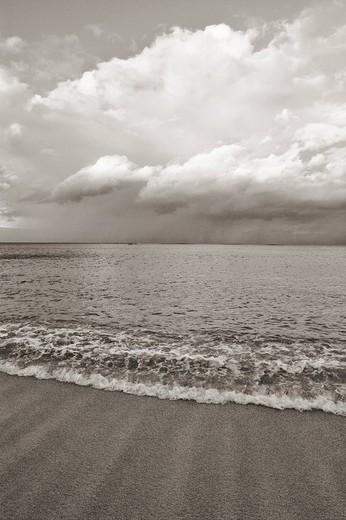 Hawaii, Oahu, Lanikai, Ocean and clouds over a sandy beach Sepia photograph : Stock Photo