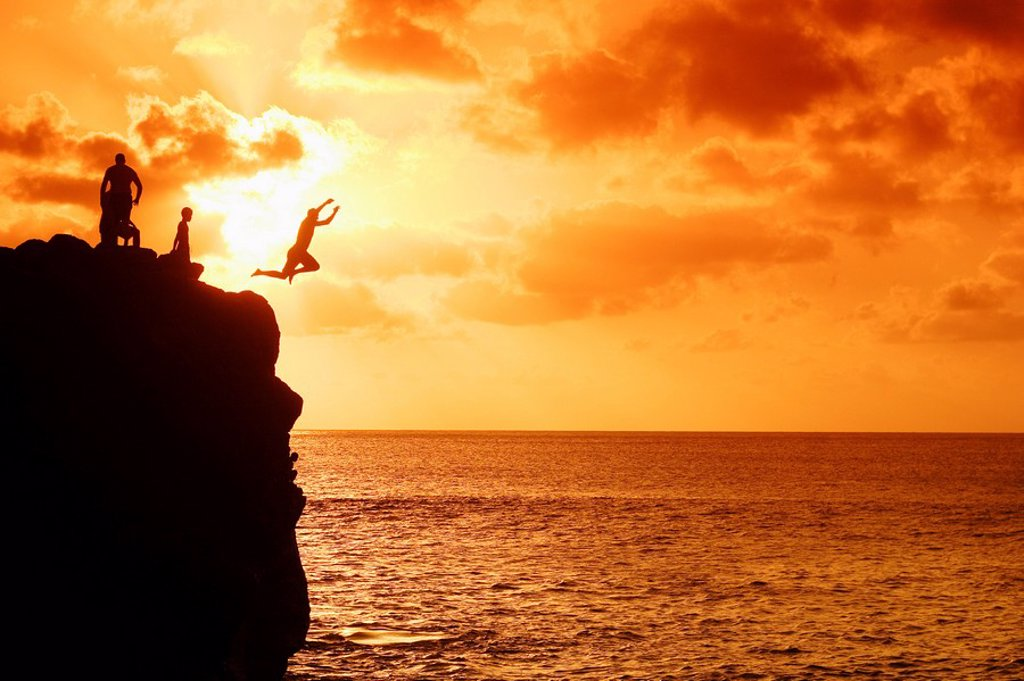 Stock Photo: 1760-6794 Hawaii, Oahu, North Shore, Waimea Bay, Silhouette of boys jumping from rock at sunset