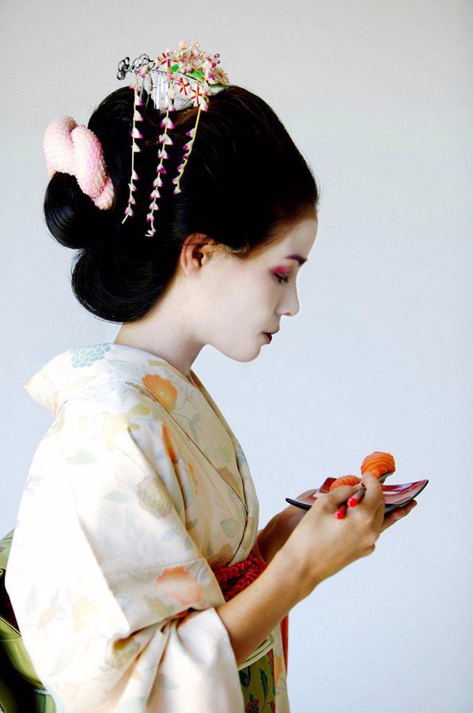 Stock Photo: 1760-8159 Portrait of traditional Japanese Maiko eating sushi.