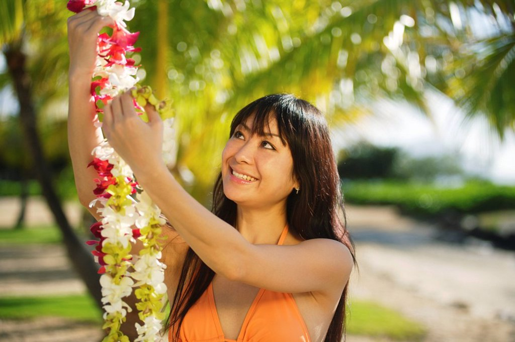 Stock Photo: 1760-8304 Young Japanese girl holding lei.