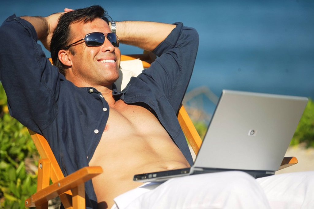 Stock Photo: 1760-8390 Hawaii, Handsome man sitting on beach with laptop computer.