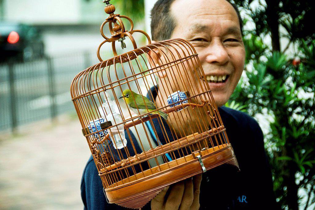 Hong Kong, Mong Kok K, A birder attends to his bird at the Yuen Po Street Bird Garden. : Stock Photo