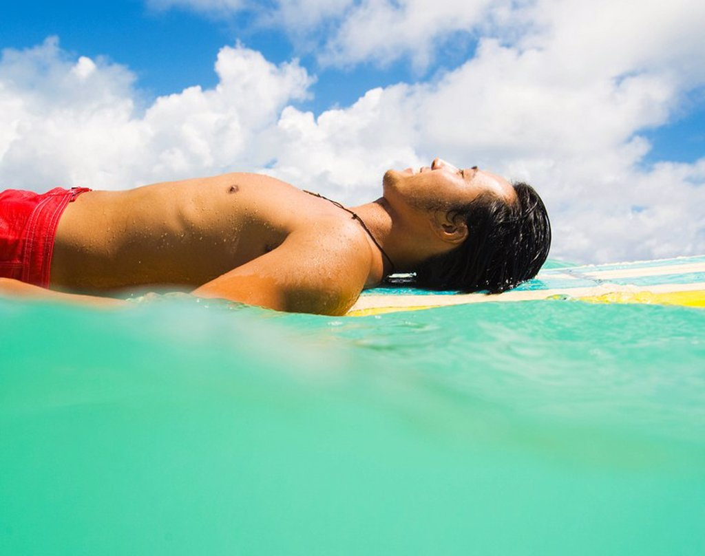 Stock Photo: 1760-8948 Hawaii, Oahu, Lanikai, Young Japanese man lying on surfboard in the ocean.