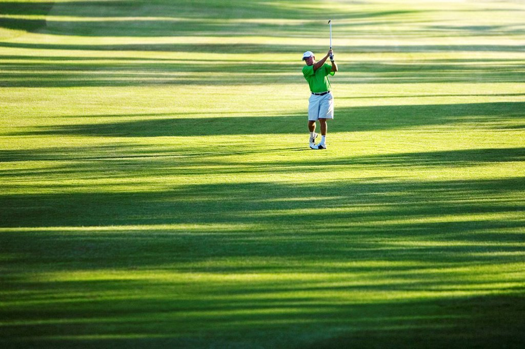 Stock Photo: 1760-9298 Hawaii, Maui, Male golfer swinging golf club at the Maui Country Club course.