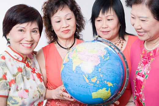 Close-up of three senior women and a mature woman holding a globe : Stock Photo