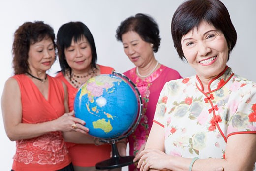 Portrait of a mature woman smiling with her friends looking at a globe : Stock Photo