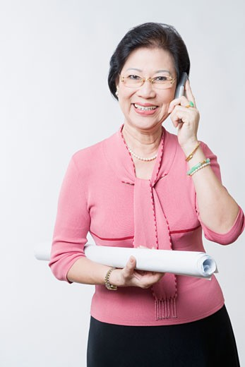 Portrait of a senior woman talking on a mobile phone and smiling : Stock Photo